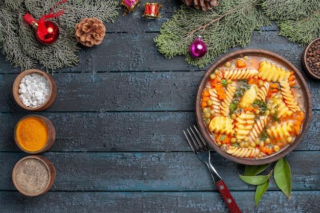 Bovenaanzicht heerlijke pastasoep van spiraalvormige italiaanse pasta met smaakmakers op de donkerblauwe bureaukeuken kleurschotel soeppasta