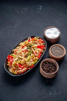 Bovenaanzicht heerlijke pepersalade binnen lang bord met kruiden donkere achtergrond maaltijd dieetschotel horizontaal kleur voedsel gezondheid brood