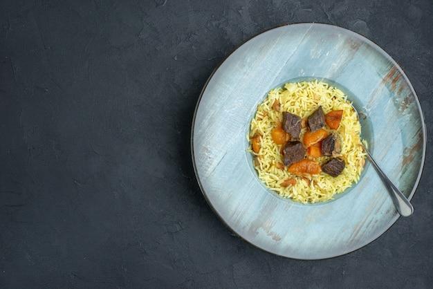 Bovenaanzicht heerlijke pilaf gekookte rijst met gedroogde abrikozen en vleesplakken binnen plaat op donkere ondergrond