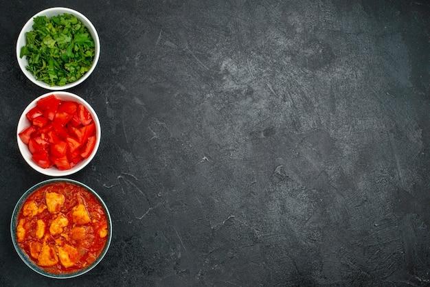 Bovenaanzicht heerlijke plakjes kip met tomatensaus en greens op donkergrijze achtergrond sausschotel vlees kip tomaat