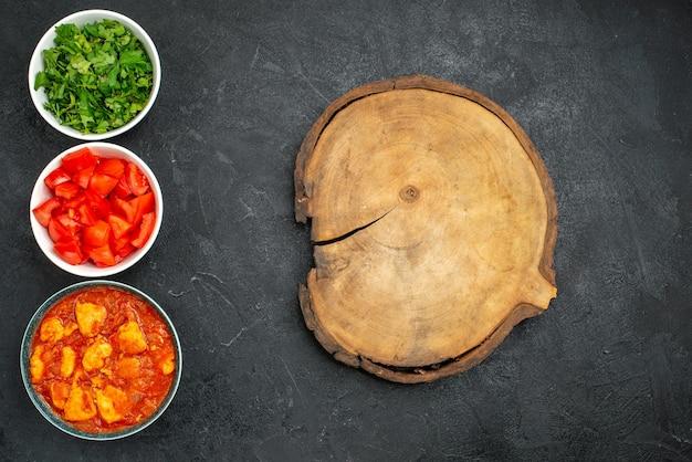 Bovenaanzicht heerlijke plakjes kip met tomatensaus en groenten op donkergrijze sausschotel kip tomatenvlees