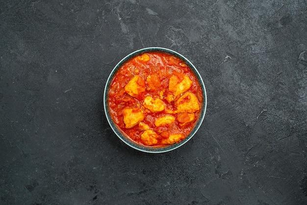 Bovenaanzicht heerlijke plakjes kip met tomatensaus op de grijze achtergrond sausschotel vlees kip tomaat