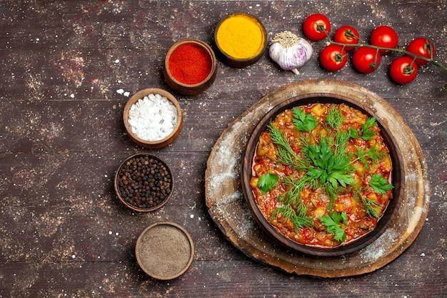 Bovenaanzicht heerlijke plantaardige maaltijd gesneden gekookte groenten met kruiden op donkere achtergrond maaltijd eten diner saus soep