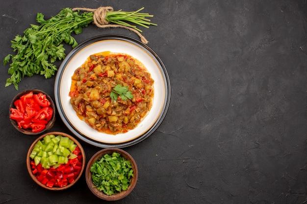 Bovenaanzicht heerlijke plantaardige maaltijd gesneden gekookte schotel in plaat op grijze achtergrond maaltijd diner eten saus soep groenten