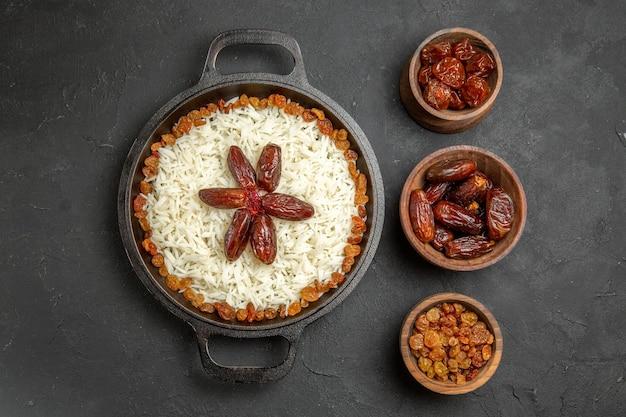 Bovenaanzicht heerlijke plov gekookte rijstmaaltijd met rozijnen in pan op het donkere oppervlak eten rijst oosterse dinermaaltijd