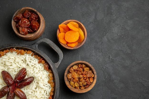 Bovenaanzicht heerlijke plov gekookte rijstmaaltijd met rozijnen op donkere oppervlakte eten rijst oosterse dinermaaltijd