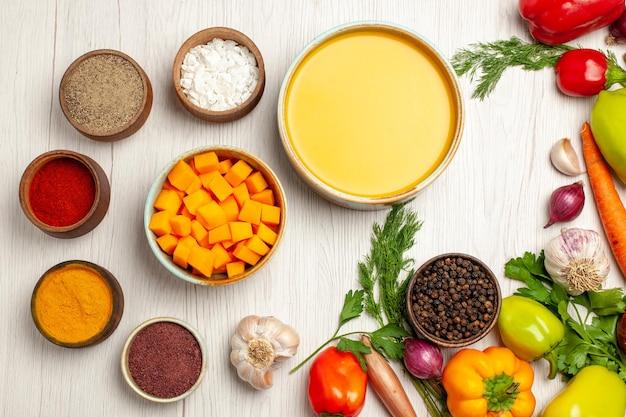 Bovenaanzicht heerlijke pompoensoepcrème getextureerd met groenten op witte bureau rijpe soepsausmaaltijd