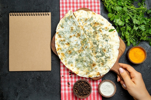 Bovenaanzicht heerlijke qutabs gekookte deegplakken met greens binnen op de grijze ruimte