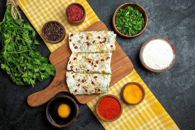 Bovenaanzicht heerlijke qutabs gekookte deegplakken met greens en verschillende kruiden op grijze ruimte