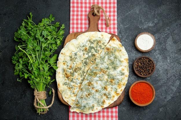 Bovenaanzicht heerlijke qutabs gekookte deegplakken met verschillende kruiden op grijze ruimte