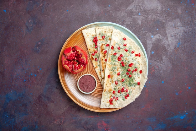 Bovenaanzicht heerlijke qutabs gekookte deegstukken met greens en granaatappels op het donkere oppervlak deegmaaltijd diner kookschotel