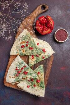 Bovenaanzicht heerlijke qutabs gekookte deegstukken met greens op donker bureau calorie vet kookschotel deeg maaltijd