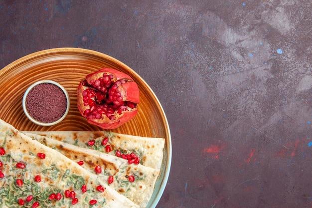 Bovenaanzicht heerlijke qutabs gekookte deegstukken met groenten en granaatappels op donkere bureaudeegmaaltijd diner kookschotel