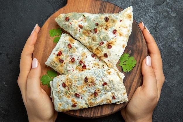 Bovenaanzicht heerlijke qutabs met verschillende kruiden op grijze vloer maaltijd koken deeg vlees voedsel olie