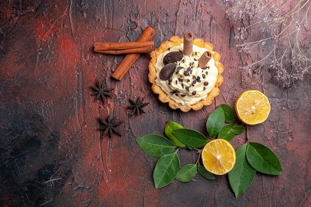 Bovenaanzicht heerlijke romige cake met citroen op donkere tafel dessert zoete koektaart