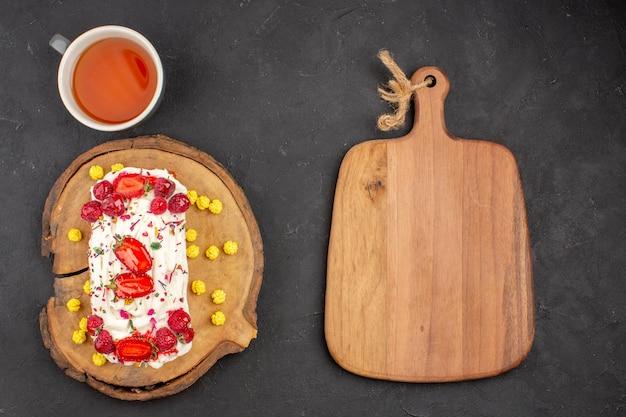 Bovenaanzicht heerlijke romige cake met fruit en kopje thee op donkere achtergrond biscuit cookie cake zoete thee cream pie