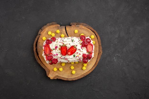 Bovenaanzicht heerlijke romige cake met fruit en snoep op de donkere achtergrond biscuit koekjes cake zoete thee cream pie