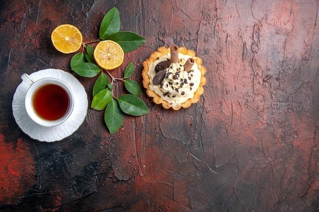 Bovenaanzicht heerlijke romige cake met kopje thee op de donkere tafel taart zoet dessert