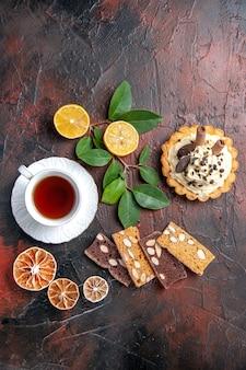 Bovenaanzicht heerlijke romige cake met kopje thee op de donkere tafel zoete cake dessert