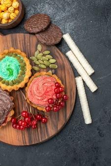 Bovenaanzicht heerlijke romige taarten met fruit op donkere tafel zoete koekkoekjes