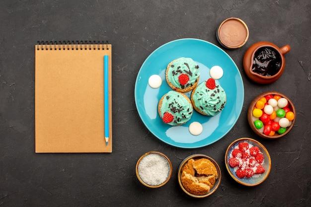 Bovenaanzicht heerlijke romige taarten met snoep op donkere achtergrond candy biscuit cake dessert cookies kleur
