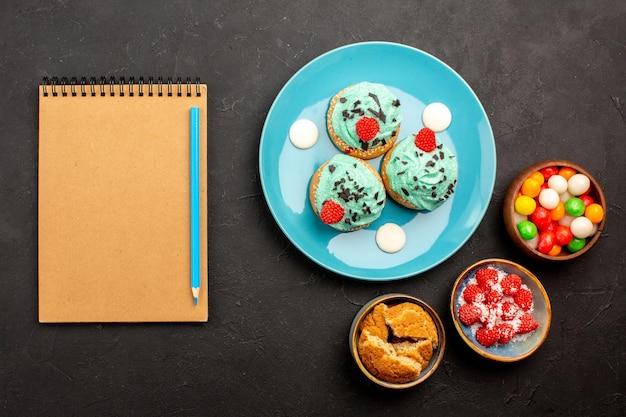 Bovenaanzicht heerlijke romige taarten met snoepjes op de donkere achtergrond cake dessert biscuit snoep koekjes kleur