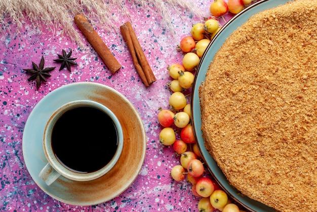 Bovenaanzicht heerlijke ronde cake binnen plaat met omzoomde zoete kersen thee en kaneel op het helderroze bureau taart taartkoekje