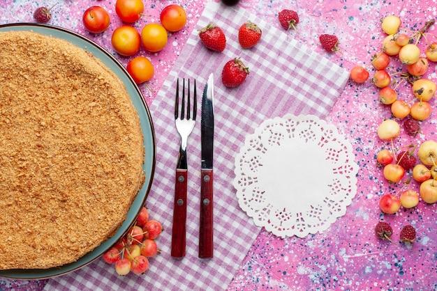 Bovenaanzicht heerlijke ronde cake binnen plaat met vers fruit op het felroze bureau taart taart biscuit zoete bak suiker