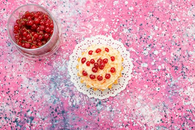 Bovenaanzicht heerlijke ronde cake met verse rode veenbessen erop en apart op de paarse bureausuiker