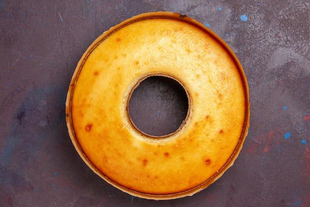 Bovenaanzicht heerlijke ronde cake perfecte zoete taart voor thee op de donkere achtergrond thee biscuit zoete taart suiker deeg cake
