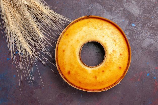 Bovenaanzicht heerlijke ronde cake perfecte zoete taart voor thee op de donkere achtergrond thee zoete taart cake suiker koekjesdeeg