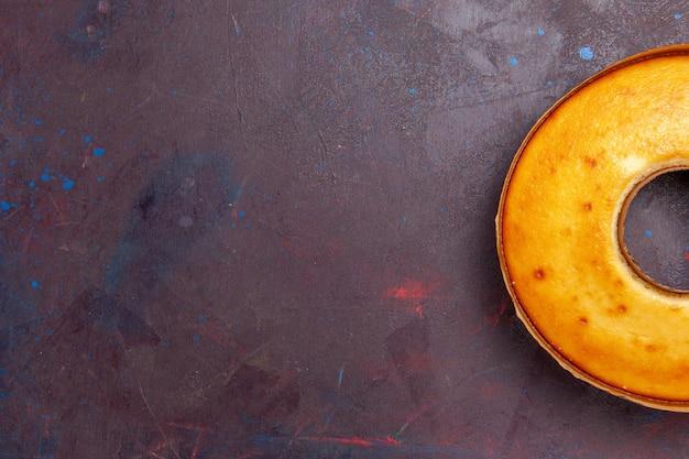 Bovenaanzicht heerlijke ronde cake perfecte zoete taart voor thee op donkere bureau thee zoete taart suiker deeg cake