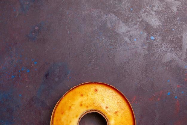 Bovenaanzicht heerlijke ronde cake perfecte zoete taart voor thee op donkere vloer thee zoete taart suiker deeg cake