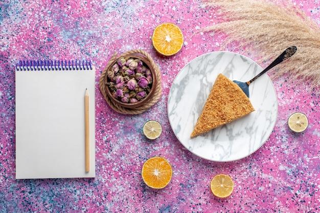 Bovenaanzicht heerlijke ronde cakeplak ervan in plaat met blocnote op het felroze bureau cake pie biscuit sweet bake