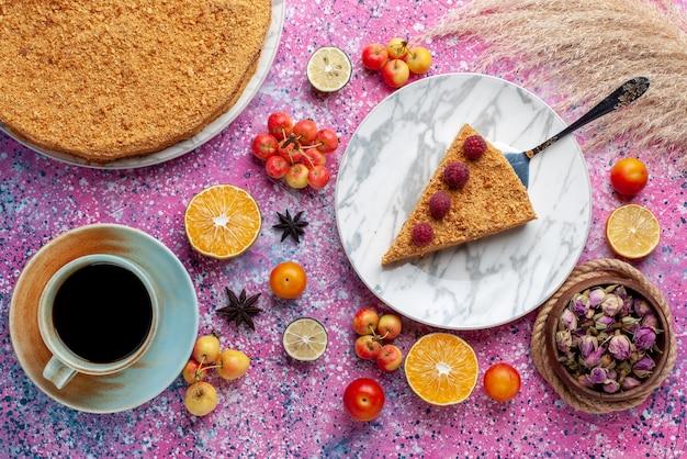 Bovenaanzicht heerlijke ronde cakeplak ervan in plaat met kopje thee op het felroze bureau cake fruittaart koekje zoet bakken