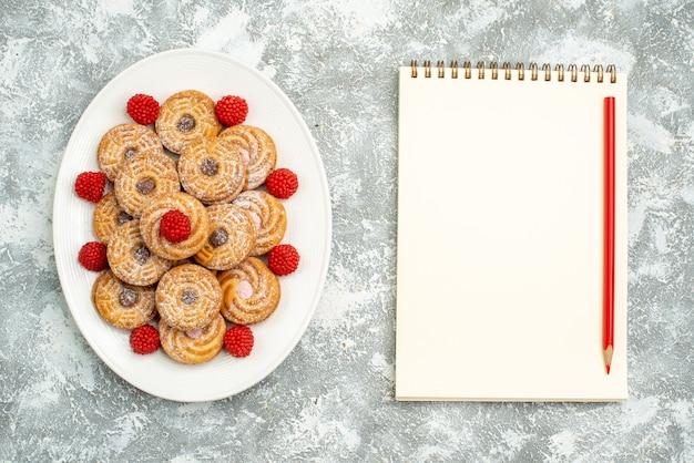 Bovenaanzicht heerlijke ronde koekjes met frambozen confitures op witte ruimte