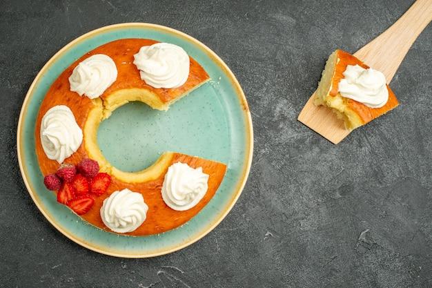 Bovenaanzicht heerlijke ronde taart gesneden met witte room op de grijze achtergrond cookie biscuit cake taart zoete thee