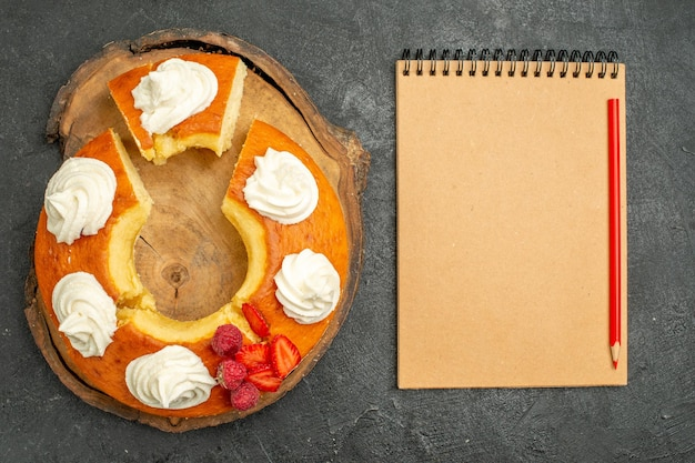 Bovenaanzicht heerlijke ronde taart gesneden met witte room op grijze achtergrond thee koekje biscuit taart taart sweet
