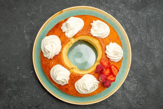 Bovenaanzicht heerlijke ronde taart met fruit en room op de donkere achtergrond thee suiker koekje biscuit cake taart zoet