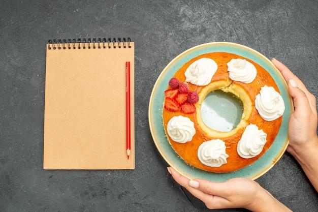 Bovenaanzicht heerlijke ronde taart met fruit en room op donkere achtergrond thee suiker koekjes biscuit cake sweet