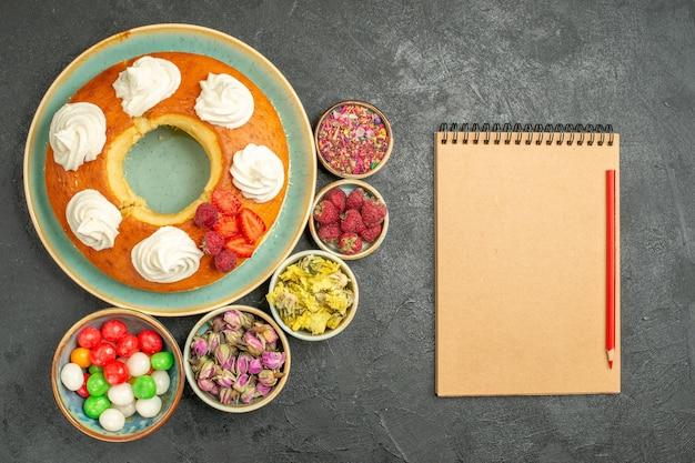 Bovenaanzicht heerlijke ronde taart met snoepjes op de grijze achtergrond suikerkoekje biscuit taart taart zoete thee