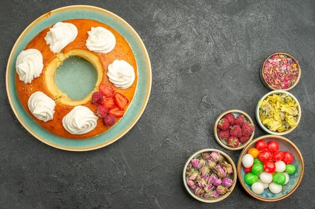Bovenaanzicht heerlijke ronde taart met snoepjes op grijs bureau suikerkoekje biscuit taart taart zoete thee