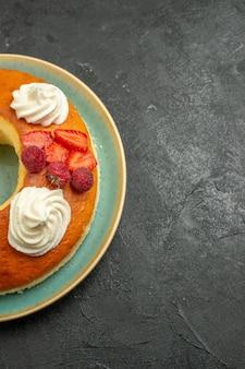 Bovenaanzicht heerlijke ronde taart met witte room op grijze achtergrond suikerkoekje biscuit taart taart zoete thee