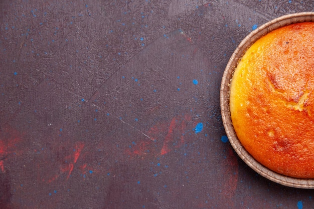 Bovenaanzicht heerlijke ronde taart zoete bak op een donkere achtergrond cake biscuit zoete taart suiker thee deeg