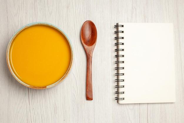 Bovenaanzicht heerlijke roomsoep geel gekleurde soep op wit bureau soepsaus maaltijd crème dinerschotel