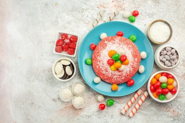 Bovenaanzicht heerlijke roze cake met kleurrijke snoepjes op het witte oppervlak regenboog kleur dessert cake snoep