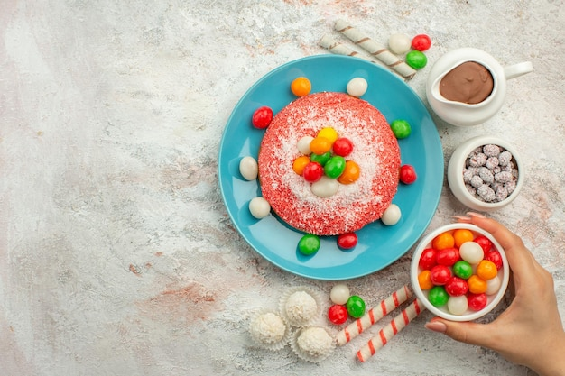 Bovenaanzicht heerlijke roze cake met kleurrijke snoepjes op witte oppervlakte dessert kleur regenboog snoep cake goodie