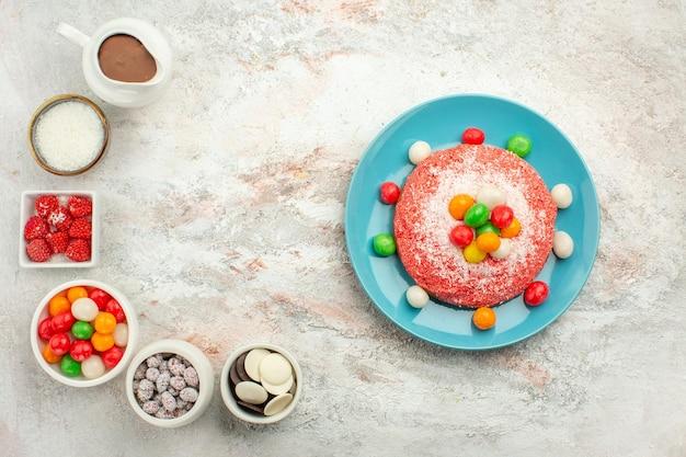 Bovenaanzicht heerlijke roze cake met kleurrijke snoepjes op witte oppervlakte kleur dessert cake regenboog snoep