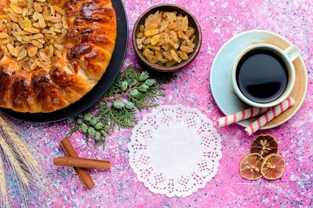 Bovenaanzicht heerlijke rozijnencake met kopje koffie op de roze achtergrond bak taart suiker zoete koekje cookie kleur