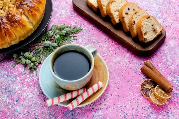 Bovenaanzicht heerlijke rozijnencake met kopje koffie op het roze bureau bak taart suiker zoet koekje koekje kleur